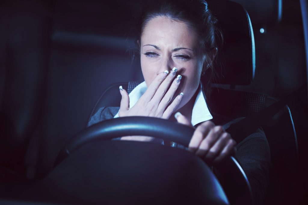 distracted exhausted tired woman driving a car late at night